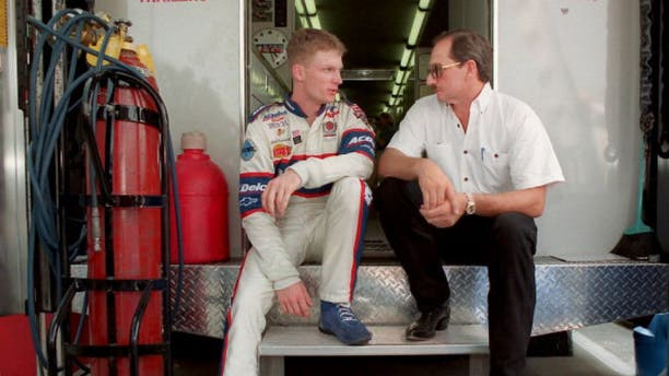 Dale Earnhardt Jr. and Dale Earnhardt Sr., sit on the back of a transporter discussing Earnhardt Jr.'s preparation for Carquest 300 Grand National qualifications on May 21, 1998 in Concord, North Carolina. (Photo by Jeff Siner/Charlotte Observer/MCT via Getty Images)