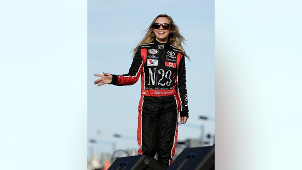 Natalie Decker waves to fans during driver introductions before starting her ARCA race at Daytona on pole position.