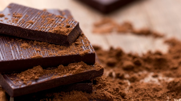 Dark Chocolate with Cocoa on Wooden Table