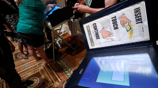 Hackers look over real voting machines in a Voting Machine Hacking Village during the Def Con hacker convention in Las Vegas, Nevada, U.S. on July 29, 2017. REUTERS/Steve Marcus - RTS19ONC