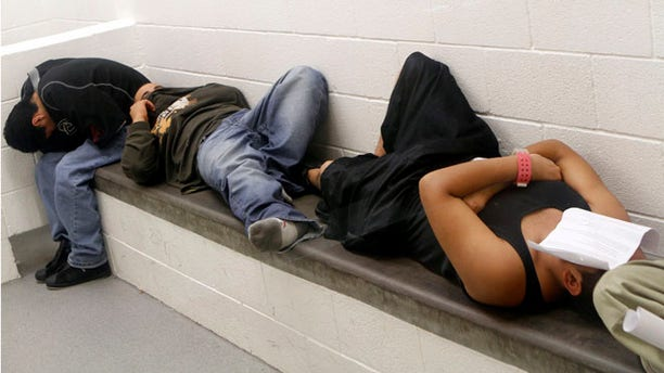 Undocumented immigrants hide their faces as they wait to be deported from the Immigration and Customs Enforcement holding facility in Phoenix May 6, 2010.