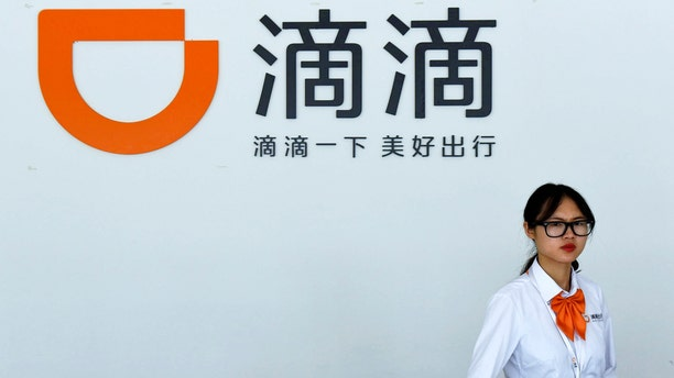 In this June 13, 2016, photo, a receptionist walks by front desk of the service station for Didi Chuxing's drivers in Hangzhou in east China's Zhejiang province.