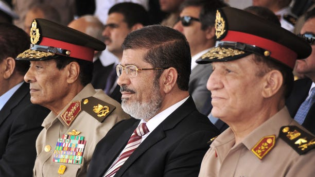 July 5, 2012: In this file image released by the Egyptian President, Egyptian Field Marshal Gen. Hussein Tantawi, left, new President Mohammed Morsi, center, and Armed Forces Chief of Staff Sami Anan, right, attend a medal ceremony, at a military base east of Cairo, Egypt. The spokesman for Egypts president says Mohammed Morsi, the countrys Islamist leader, has decided to retire the head of the Armed Forces and minister of Defense and chief of staff.