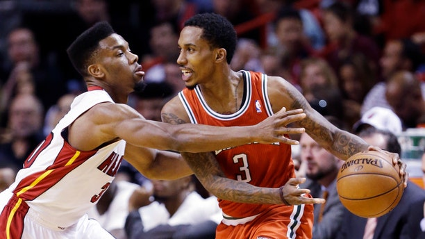 Miami Heat guard Norris Cole, left, defends against Milwaukee Bucks guard Brandon Jennings during the first half of an NBA basketball game, Tuesday, April 9, 2013, in Miami. (AP Photo/Wilfredo Lee)