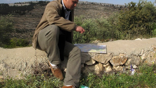 In this Friday, April 19, 2013 photo, George Abu Eid, 22, sits with the map of the area near the village of Beit Jala in the Cremisan Valley, West Bank. Abu Eid's family land is threatened with expropriation to build Israel's separation barrier. Palestinian residents of this Christian village are hoping the new pope can succeed where others have failed as they press the Israeli government to drop plans to build a stretch of its West Bank separation barrier through their ancestral lands. (AP Photo/Diaa Hadid)