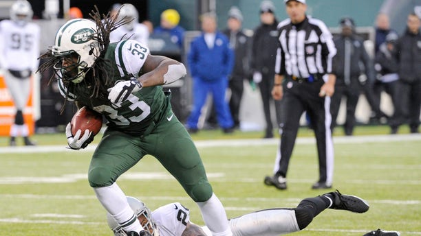 FILE - In this Dec. 8, 2013 file photo, New York Jets running back Chris Ivory (33) breaks away from Oakland Raiders safety Charles Woodson during the second half of an NFL football game, in East Rutherford, N.J. Ivory's carries the ball like a man possessed. (AP Photo/Bill Kostroun), File