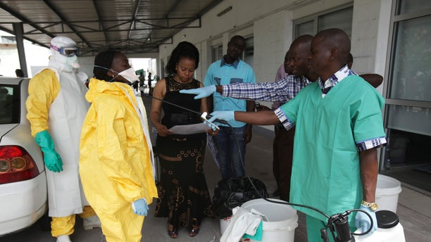 A health worker sprays a colleague with disinfectant during a training session for Congolese health workers to deal with Ebola virus in Kinshasa October 21, 2014. REUTERS/Media Coulibaly