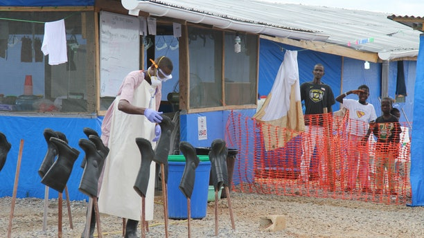 "Boys Solomon (C, rear) and Joe (R, rear) stand in the ""red zone"" where they are being treated for Ebola at the Bong County Ebola Treatment Unit about 200 km (120 miles) east of the capital, Monrovia, October 28, 2014.  REUTERS/Michelle Nichols"