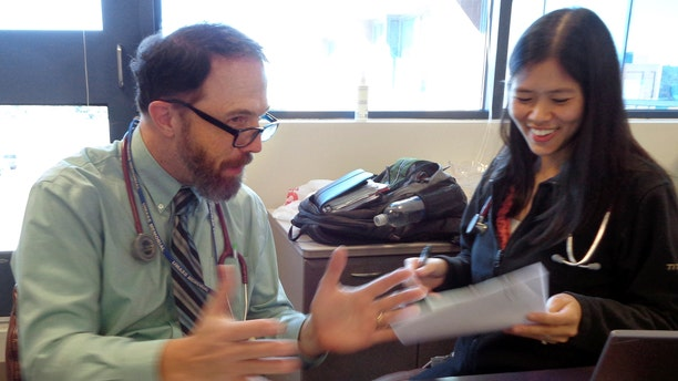 Sept. 23, 2015: In this photo, Dr. Rick Sacra reviews patient cases with Dr. Anna Chon at the Family Health Center in downtown Worcester, Mass., where he advises doctors in training.