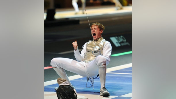FILE -- Race Imboden, of the United States, celebrates after winning a men's individual foil round 8 qualifying match against Germany's Peter Joppich at the World Fencing Championship in Catania, Italy, Thursday, Oct. 13, 2011.