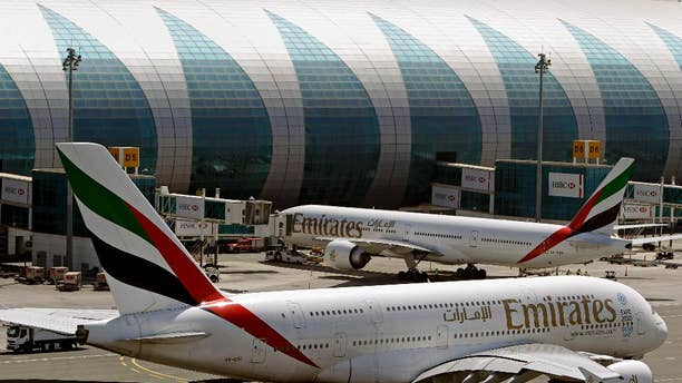 FILE- In this May 8, 2014 file photo, Emirates passenger planes are in use at Dubai airport in United Arab Emirates. The Mideast's biggest airline that touts onboard luxuries like showers and an extensive movie selection is adding something a bit more down-to-earth for those in the back of the plane: charges to pick your own seat ahead of time. The change brings Emirates in line with what many other international carriers have done for years, generating a new revenue stream for the government-owned airline. (AP Photo/Kamran Jebreili, File)