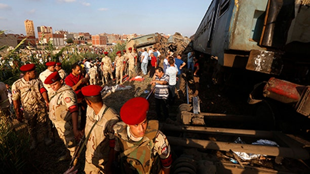 Army attend the scene of a train collision just outside Egypt's Mediterranean port city of Alexandria, Friday.