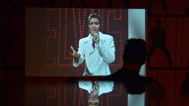 "File photo - A man watches a video of Elvis Presley performing during the grand opening of ""Elvis Presley's Memphis"", a $45 million, state-of-the-art entertainment and museum complex, in Memphis, Tennessee, U.S., March 2, 2017. (REUTERS/Brandon Dill)"