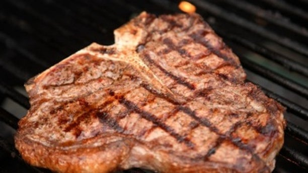 t-bone steak cooking on an open flame grill