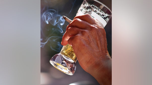 an old man sitting at the table in outdoor pub Drinking beer and smoking