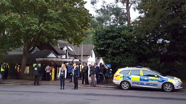 Police and evacuated visitors stand outside London Zoo after a gorilla escaped in London, Thursday, Oct. 13, 2016.