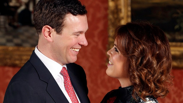Britain's Princess Eugenie and Jack Brooksbank pose for the media in the Picture Gallery at Buckingham Palace after they announced their engagement in London, Monday, Jan. 22, 2018. Princess Eugenie is engaged to be married later this year, several months after her cousin Prince Harry's nuptials.