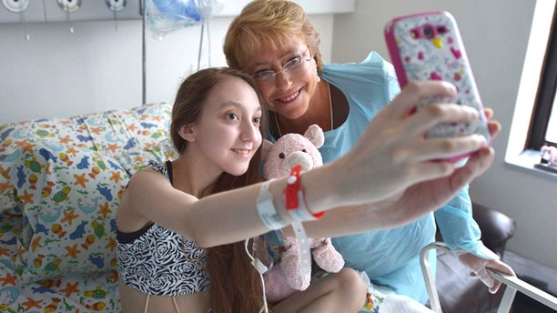 Feb. 28, 2015: In this photo released by Chile's Presidential Press Office, Valentina Maureira takes a photo of herself with President Michelle Bachelet, at the Catholic University hospital in Santiago, Chile.