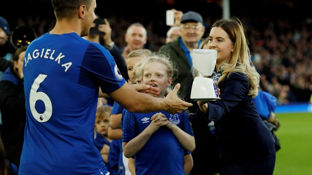 Everton captain Phil Jagielka collects the robot mascot before the match