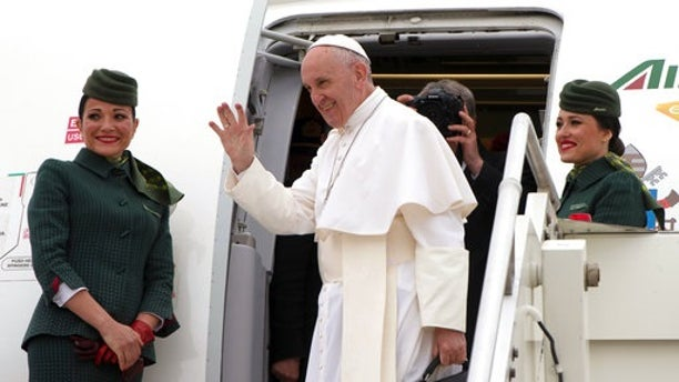 Pope Francis waves as he boards a plane on his way to Cairo, Egypt, at Rome's Fiumicino inernational airport, Friday, April 28, 2017. Francis is travelling to Egypt for a two-day trip aimed at presenting a united Christian-Muslim front that repudiates violence committed in God's name. (L'Osservatore Romano/Pool Photo via AP)