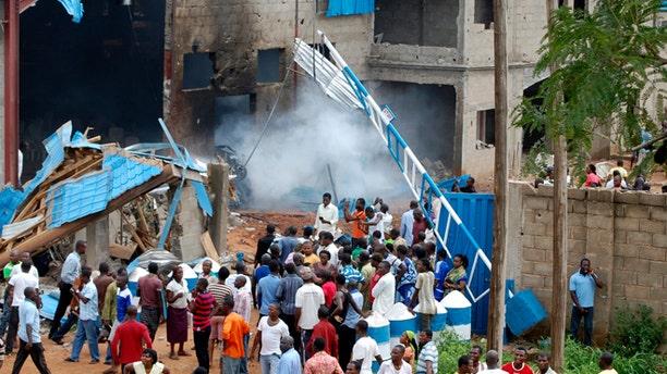 June 17, 2012: People gather outside a church following a blast in Kaduna, Nigeria.