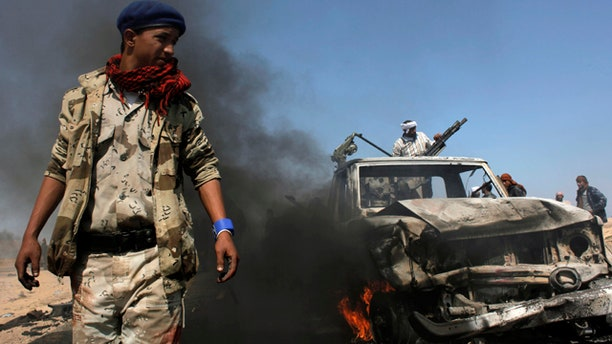 April 5: Libyan rebels inspect two destroyed military vehicles of pro-Qaddafi forces that rebels claim were targeted by a NATO strike along the front line near Brega, Libya.