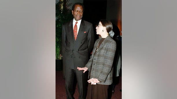 """Actor Sidney Poitier (L) chats with Supreme Court Justice Ruth Bader Ginsburg before the premiere of the film, """"Mandela and de-Klerk,"""" in which Poitier plays the role of Nelson Mandela, 1997."""