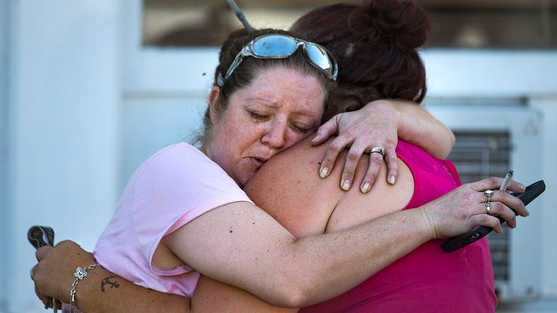 Carrie Matula embraces a woman after a fatal shooting at the First Baptist Church.