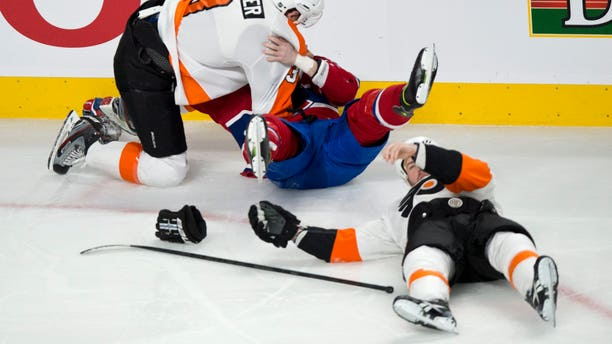 Philadelphia Flyers' Kurtis Foster charges Montreal Canadiens' Ryan White as Flyers' Kent Huskins lies on the ice after taking a hit from White during the first period of an NHL hockey game on Monday, April 15, 2013 in Montreal. (AP Photo/The Canadian Press, Paul Chiasson)