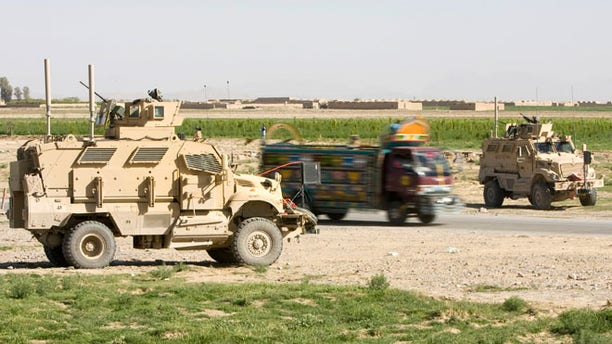 March 25, 2010: An Afghan truck is driven past U.S. Army Mine Resistant Ambush Protected (MRAP) armored vehicles of 508th Special Troops Battalion, 82nd Airborne Division, at an Afghan Police checkpoint on the Highway One, the main Afghan road around the country, outside the town of Kandahar, southern Afghanistan.  Police and sheriff's departments in the U.S. have obtained 165 MRAP vehciles leftover from the Iraq war.