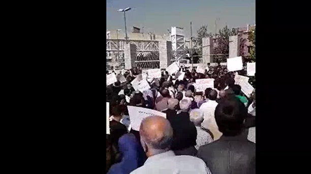 More than 2,000 Iranians protested the country's parliament because of plundered savings and corrupt policies.