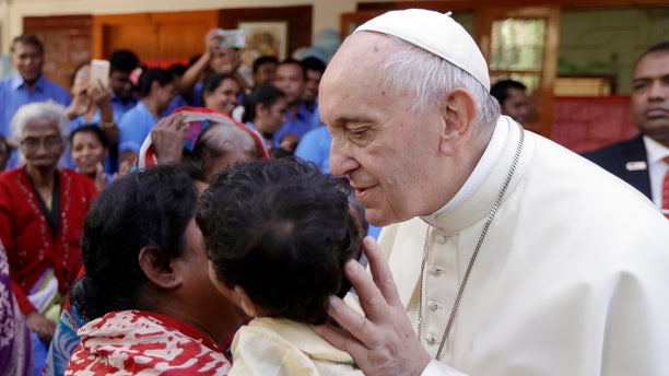 Pope Francis kisses a child as he meets with sick people and staff of the Mother Teresa House in Dhaka's Tejgaon neighborhood, Bangladesh, Dec. 2, 2017.