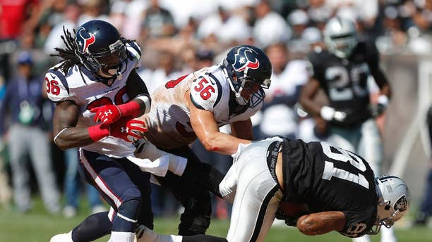 Oakland Raiders tight end Mychal Rivera, right, is brought down with the ball by Houston Texans inside linebacker Brian Cushing (56) as Texans strong safety D.J. Swearinger (36) looks on in the third quarter of an NFL football game Sunday, Sept. 14, 2014, in Oakland, Calif. (AP Photo/Beck Diefenbach)