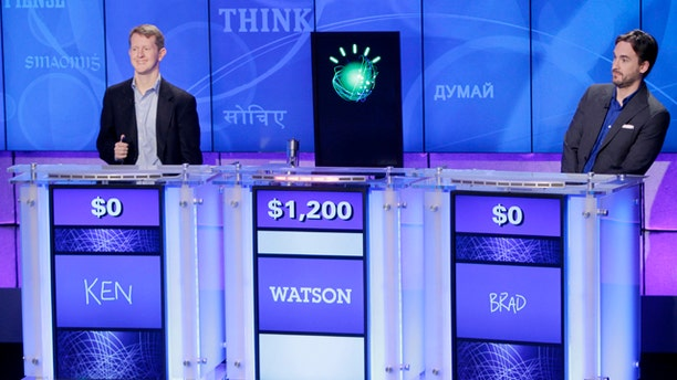 """Jeopardy!"" champions Ken Jennings, left, and Brad Rutter, right, look on as an IBM computer called ""Watson"" beats them to the buzzer to answer a question during a practice round of the ""Jeopardy!"" quiz show in Yorktown Heights, N.Y., Thursday, Jan. 13, 2011."