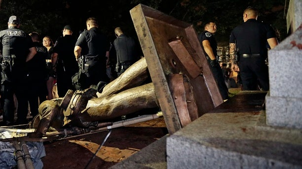 "Police stand guard after ""Silent Sam"" was toppled by protesters on campus at the University of North Carolina in Chapel Hill, N.C."