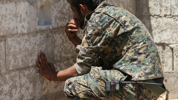 A U.S.-backed Syrian Democratic Forces fighter looks through a hole on the front line of the industrial district on the eastern side of Raqqa.
