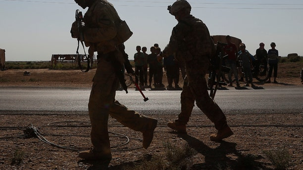 U.S. soldier, foreground, walk in front of Syrian children in the background, at a road that links to Raqqa, northeat Syria, July 26, 2017.