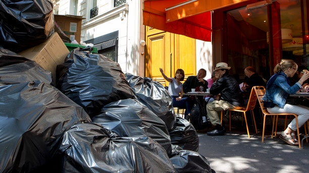 People have lunch next to overflowing trash bags in Paris on Thursday.