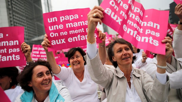 "Oct. 23, 2012: In this file photo, anti-gay marriage and gay adoption rights activists hold posters reading:  ""Mother - Father. Don't lie to your children"" demonstrate in Paris. A plan to legalize same-sex marriage and allow gay couples to adopt was a liberal cornerstone of French President Francois Hollande's election manifesto earlier this year."