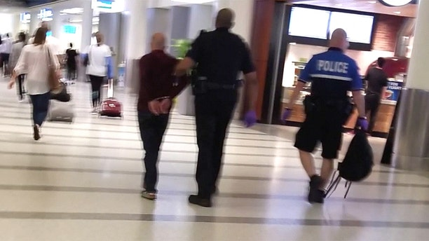 A passenger later photographed a man being led away from the gate in handcuffs.
