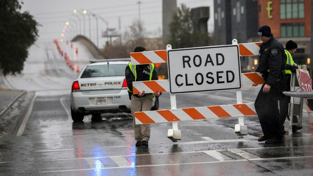 Two Savannah Chatham Metro Police officers set up a barricade in front of a bridge that was closed due to ice on the road, Wednesday, Jan. 3, 2018, in Savannah, Ga.