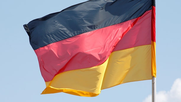 File photo - The German national flag is seen on a sunny day surrounded by some clouds at the Chancellery in Berlin, Germany, April 29, 2016. (REUTERS/Fabrizio Bensch)