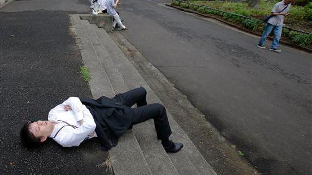 """A man takes a nap as he takes advantage of a break of the rainy season at Hibiya Park in Tokyo, Tuesday, June 10, 2014. Is he """"violating spatial norms""""?"""