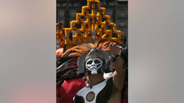 A man with his face painted and dressed as an Aztec Indian gestures during the celebration of the Day of the Dead, in Mexico City, Wednesday, Nov. 2, 2016.