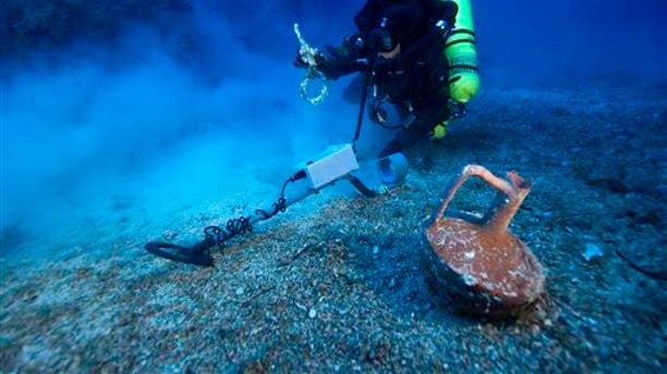 In this undated photo provided by Argo via the Greek Culture Ministry on Thursday, Oct. 9, 2014, a diver with a metal detector holds a copper ship's fitting next to a vase at the site of the Antikythera wreck off the island of Antikythera in southern Greece.