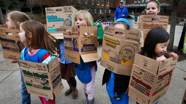 In a Feb. 18, 2013 file photo dressed in boxes emptied from earlier cookie sales, Girl Scouts from Troop 20337 in Eugene  fan out on the University of Oregon campus near the Erb Memorial Union in Eugene, Ore., in search of customers for their cookies. Just a year after its 2012 centennial celebrations, the Girl Scouts of the USA's interconnected problems include declining membership and revenues, a dearth of volunteers, rifts between leadership and grass-roots members, a pension plan with a $347 million deficit, and an uproar over efforts by many local councils to sell venerable summer camps.