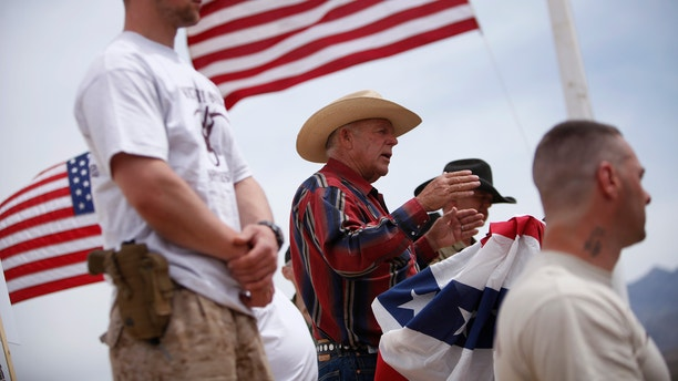 Rancher Cliven Bundy, flanked by armed supporters, at a protest camp near Bunkerville, Nev., in 2014.