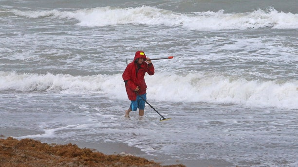 Local resident Mike Squillace looking for metal at Dania Beach, Fla., as Tropical Storm Gordon pass by South Florida with wind gust and heavy rainfall for the Labor Day holiday on Monday, Sept. 3, 2018.