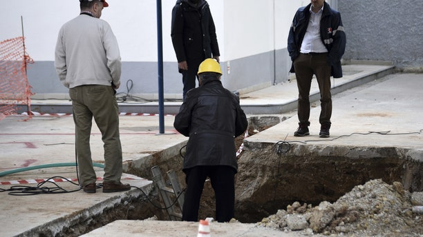 Experts check the location where an unexploded World War II bomb was found 5 meters (over 16 feet) deep, at a gas station in the northern Greek city of Thessaloniki, on Thursday, Feb. 9, 2016.