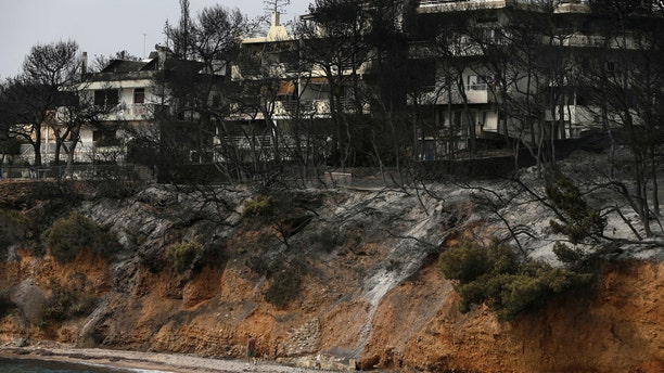 A man walks on the beach where burned trees hug the coastline in Mati east of Athens, Tuesday, July 24, 2018. Twin wildfires raging through popular seaside areas near the Greek capital have torched homes, cars and forests and killed at least 49 people, authorities said Tuesday, raising the death toll after rescue crews reported finding the bodies of more than 20 people huddled together near a beach. (AP Photo/Thanassis Stavrakis)